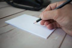 在空的笔记本的男性手文字 免版税库存照片