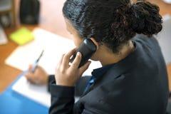 Ρεσεψιονίστ που χρησιμοποιεί το τηλέφωνο στην αρχή Στοκ Εικόνες