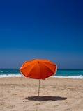 在海滩的橙色遮阳伞 免版税库存照片