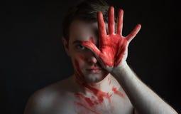 有血液的人在他的面孔和棕榈 库存图片