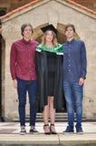 女孩与双兄弟姐妹的毕业典礼举行日 免版税图库摄影