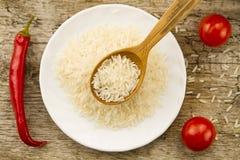 在一把木匙子在背景板材,辣椒,西红柿的长粒米 健康吃,饮食 免版税库存照片
