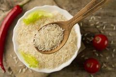 在一把木匙子在背景板材,辣椒,西红柿的长粒米 健康吃,饮食 免版税库存图片