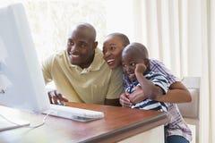 聊天与计算机的愉快的微笑的家庭 免版税库存图片