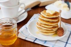 堆薄煎饼用蜂蜜糖浆、黄油和草莓在一块白色板材 库存照片