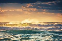 日出和发光在海洋挥动 免版税库存图片