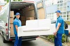 投入家具和箱子的工作者在卡车 免版税库存图片