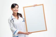 拿着空白的委员会的微笑的医生 免版税库存图片