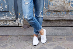 女孩在运动鞋盘着腿站立 库存照片