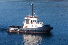 用力拖有白色超结构和深蓝船身的小船 免版税图库摄影