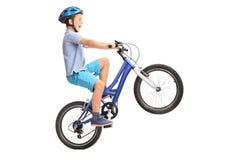 做在一辆小蓝色自行车的小男孩一个自行车前轮离地平衡特技 库存照片