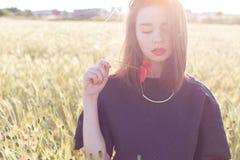 有大嘴唇的美丽的性感的逗人喜爱的女孩和在一件黑夹克的红色唇膏有站立在鸦片的花鸦片的调遣在日落 免版税库存图片