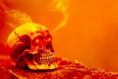Αφηρημένο κρανίο στον πορτοκαλή τόνο με να λάμψει ματιών το φως και τον καπνό Στοκ Εικόνες
