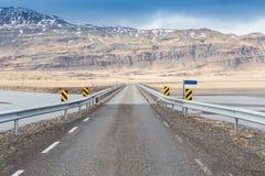 乡下公路通过积雪的山 免版税图库摄影