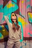 摆在片段附近的五颜六色的太阳镜的时髦的十几岁的女孩 图库摄影
