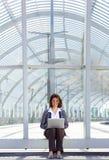 坐外面使用膝上型计算机的微笑的女商人 免版税库存图片