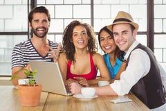 站立在膝上型计算机附近的微笑的朋友 免版税库存图片