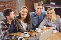 喝咖啡和使用的微笑的朋友膝上型计算机 免版税图库摄影