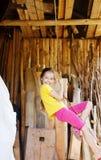 逗人喜爱的小女孩是使用和摇摆在绳索户外在夏天 免版税库存照片
