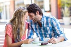 坐在咖啡馆的逗人喜爱的夫妇势均力敌 库存照片