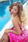 时尚桃红色礼服的美丽的白肤金发的式样女孩有构成的和 免版税库存照片