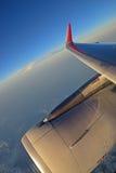 涡轮发动机、翼和红色小翅膀与白色云彩和深蓝天在背景中 免版税图库摄影