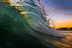 打破在日落日出的海浪 免版税库存图片