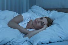 妇女在遭受失眠的床上 免版税库存图片