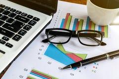 在书桌办公室和图表分析报表的膝上型计算机 免版税库存照片