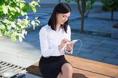 与智能手机的女商人听的音乐在城市公园 库存照片