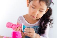 Το μικρό κορίτσι μαθαίνει να χρησιμοποιεί τη ζωηρόχρωμη ζύμη παιχνιδιού Στοκ Φωτογραφίες