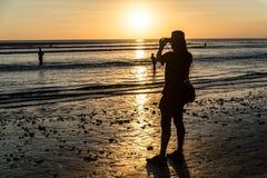 拍日落照片的旅行家在库塔海滩,巴厘岛 免版税库存图片