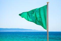 在海滩的绿色旗子在明亮的蓝色海 免版税库存照片