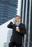 Νέος ελκυστικός επιχειρηματίας στο κοστούμι και δεσμός που μιλά στο κινητό τηλέφωνο ευτυχές υπαίθρια Στοκ Φωτογραφία