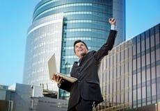 与计算机膝上型计算机愉快的做的胜利标志的成功的商人 免版税库存照片