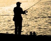 站立在船坞边缘的渔夫有钓鱼竿的在河附近在城市 免版税库存照片