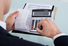 拿着收据的商人,当计算费用在办公室时 免版税库存照片