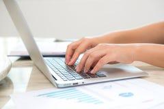 键入在膝上型计算机键盘的女商人手 库存图片