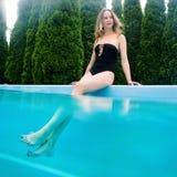 在游泳池附近的年轻美丽的妇女 免版税库存照片