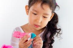 Το μικρό κορίτσι μαθαίνει να χρησιμοποιεί τη ζωηρόχρωμη ζύμη παιχνιδιού Στοκ Εικόνα