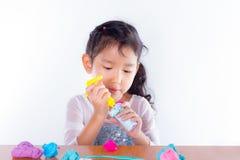 Το μικρό κορίτσι μαθαίνει να χρησιμοποιεί τη ζωηρόχρωμη ζύμη παιχνιδιού Στοκ φωτογραφία με δικαίωμα ελεύθερης χρήσης