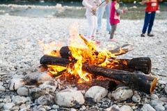 享受时间的家庭由河和自制营火 免版税库存照片