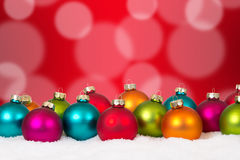 许多与雪的五颜六色的圣诞节球背景装饰 库存照片
