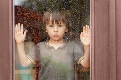在窗口后的小男孩在雨中 免版税库存图片