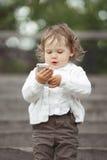 使用与手机的小女孩 免版税库存照片