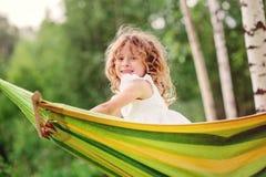 获得乐趣和放松在吊床的愉快的儿童女孩在夏天 免版税库存照片