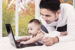 有演奏膝上型计算机的爸爸的好奇婴孩 库存照片