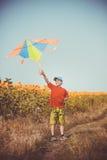 跑横跨与飞行在他的头的风筝的领域的男孩 免版税库存图片