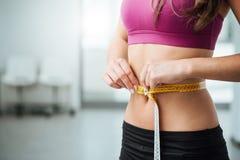 Тонкая женщина измеряя ее тонкую талию Стоковые Фотографии RF