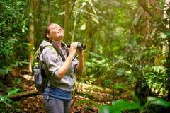 观看通过双筒望远镜野生鸟的远足者在密林 库存图片